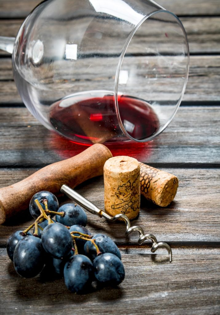 Wine background. A glass of red wine with a corkscrew and a vine.